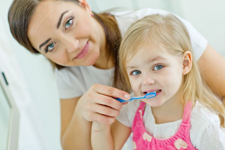 Mom and Daughter brushing their teeth - Pediatric Dentist in St. Louis, MO